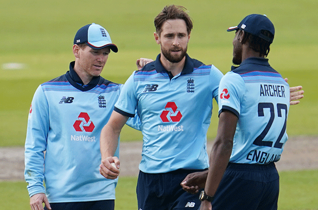 Chris Woakes is congratulated by captain Eoin Morgan and Jofra Archer